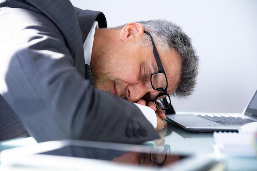 Man lying on his desk asleep.