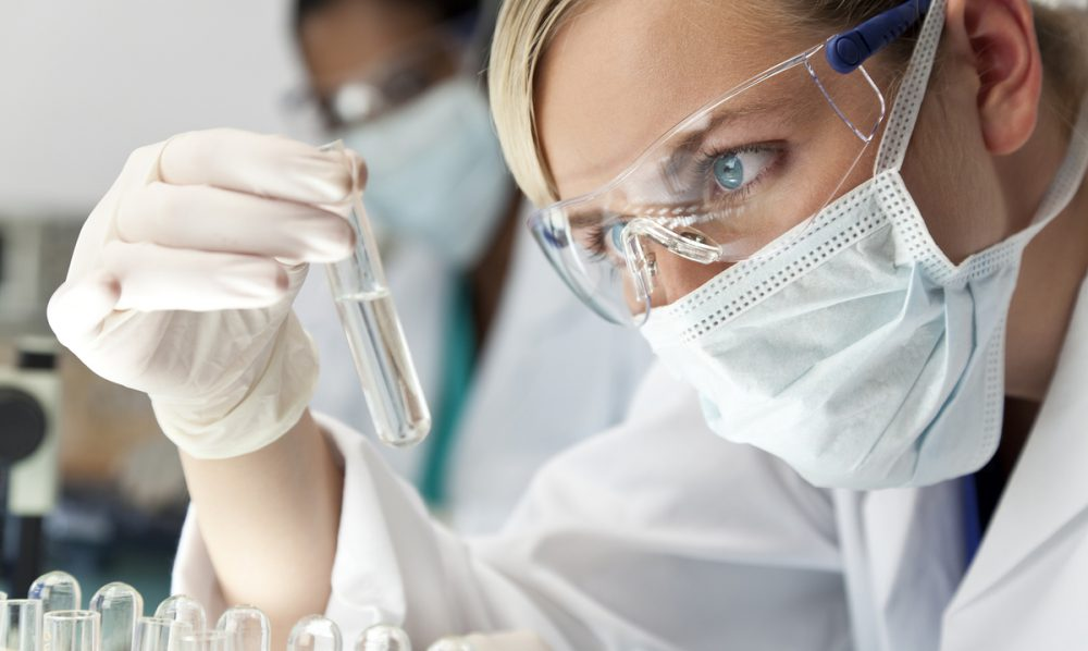 Medical technician looking at liquid in a glass vial.