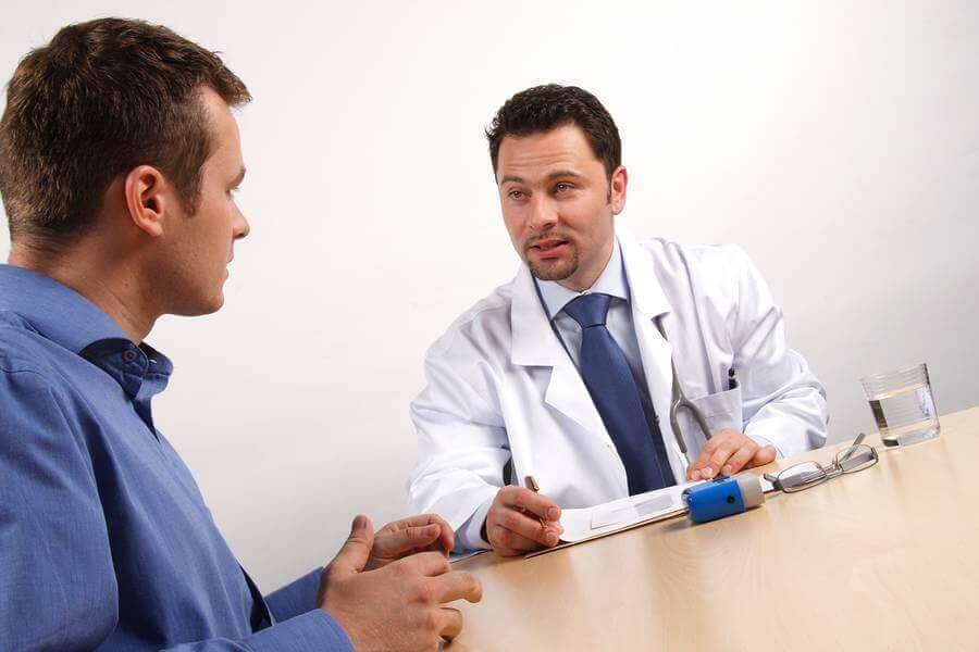 Medical doctor discussing care with a male patient at a table.