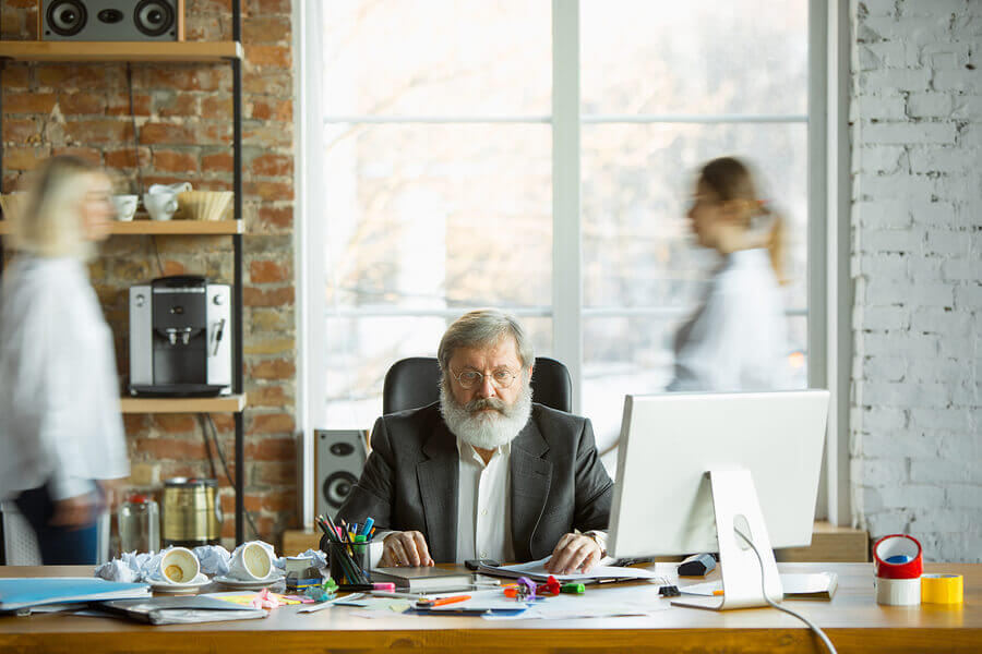 Man sitting at a desk filled with papers and a desktop computer.