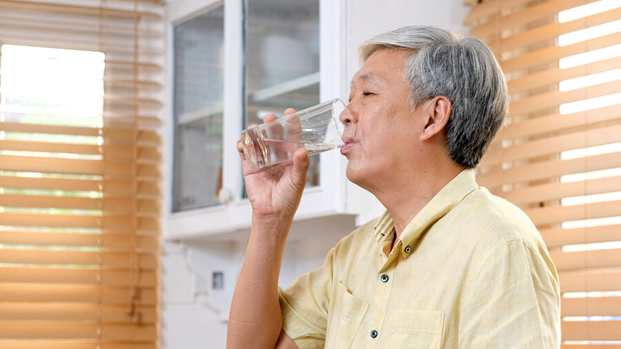 Man drinking a glass of water.