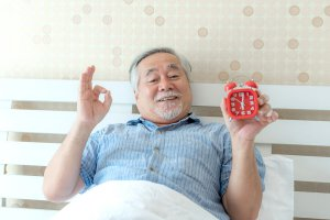 Man giving the OK sign with his hand while holding an alarm clock in the other.