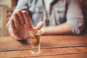 Person holding their hand out in front of a shot glass filled with amber liquid.