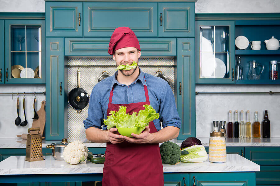 Man holding a bowl of lettuce while wearing a red apron and cap.