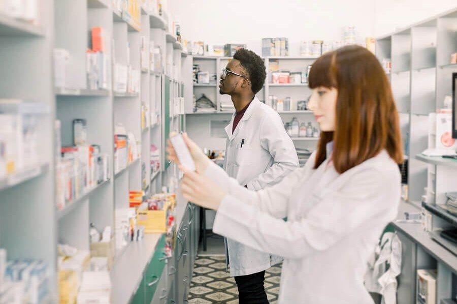 Two pharmacists stocking shelves.