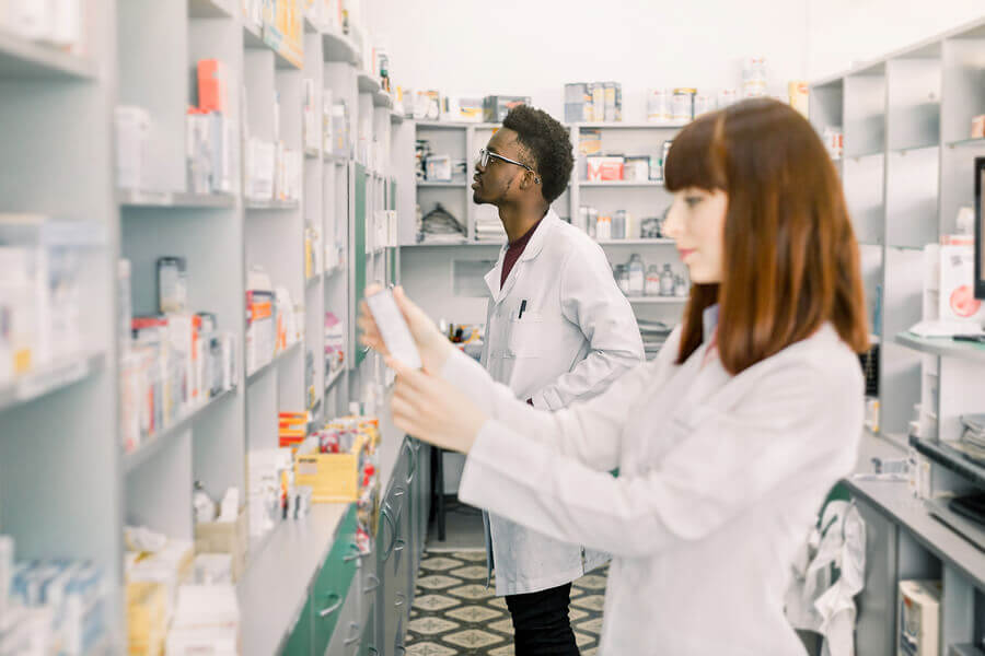 Two pharmacists stocking shelves.