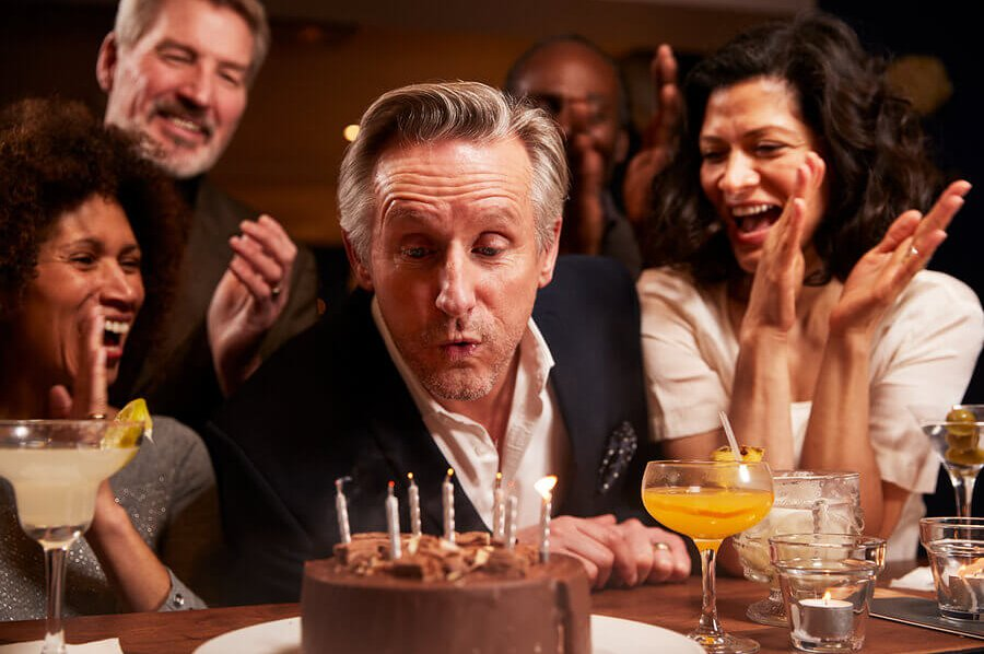 Man blowing out birthday candles on a chocolate cake.