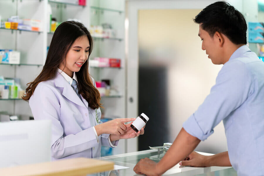Man purchasing medication from a pharmacist at a counter.