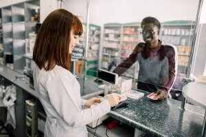 Person filling a prescription with a pharmacist.