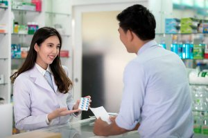 Pharmacist filling a prescription for a customer.