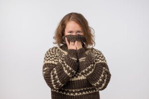 Woman wearing a sweater and covering her face with it.