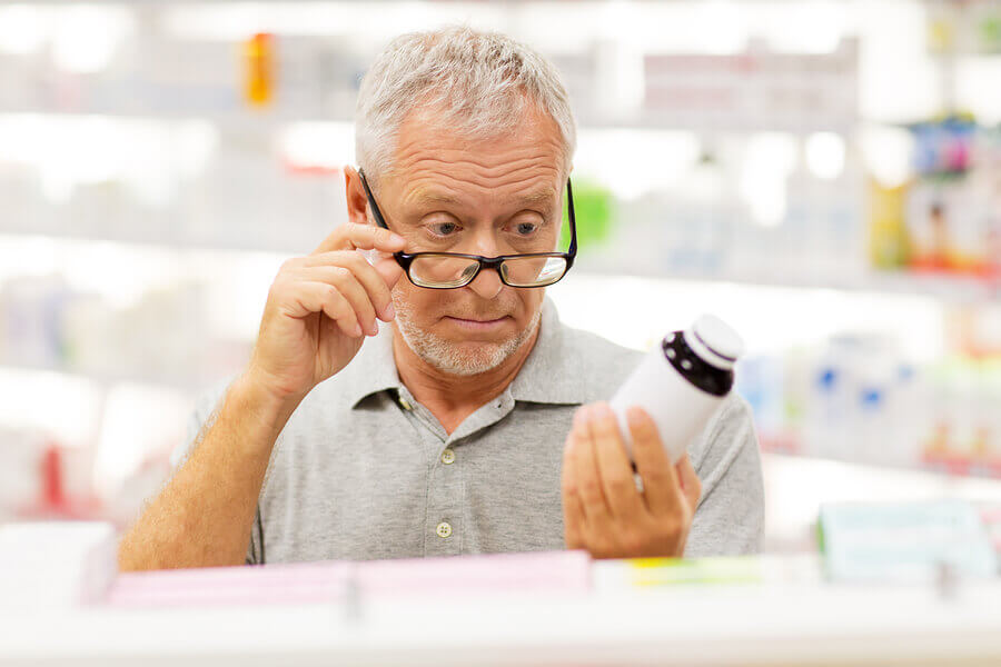 Man looking at a label on a pill bottle