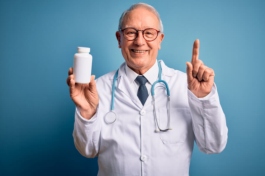 Medical doctor holding a bottle of medication.