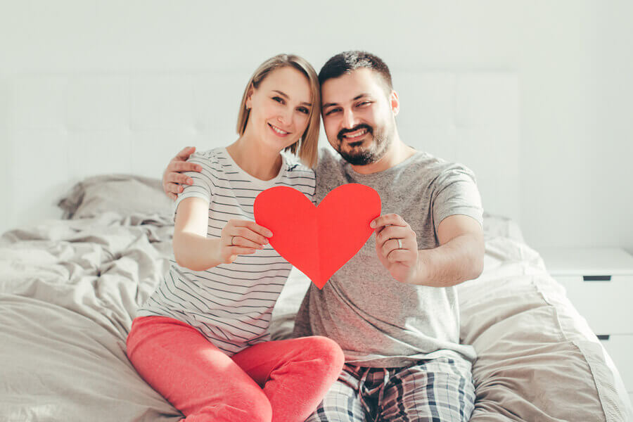 Couple holding a red paper heart.