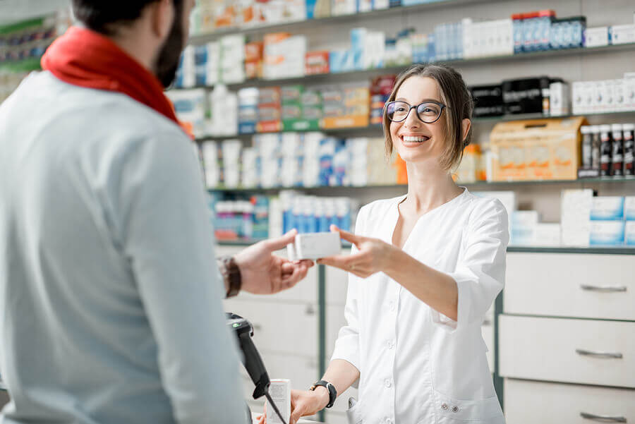Pharmacist handing medication to a customer.