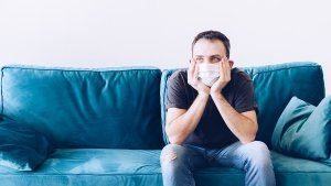Man wearing a face mask sitting on a couch.