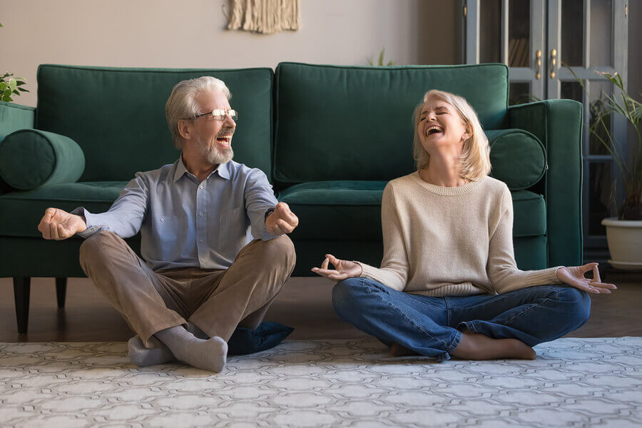 Couple smiling at each other in a cross legged position.