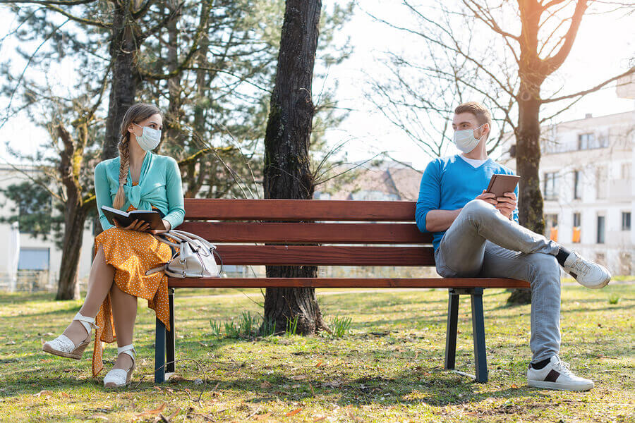 Two people siting at either end of a park bench.