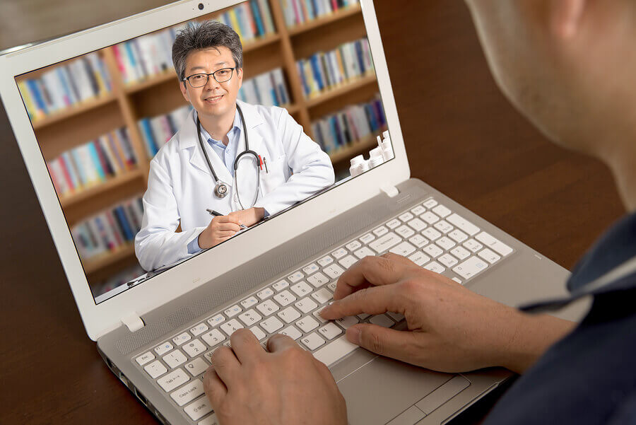 Medical doctor discussing care with a patient using a laptop.