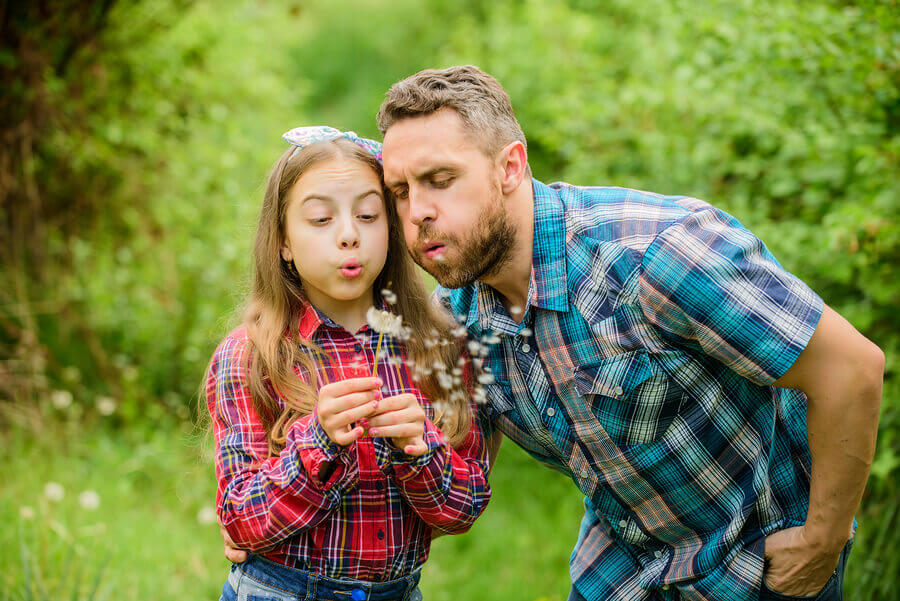 Father and daughter blowing on a dandelion.