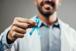 Medical doctor holding a blue ribbon.
