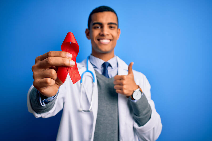 Medical doctor smiling while holding a red ribbon.