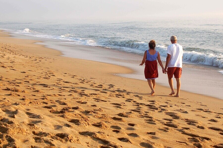 Couple walking on a beach.