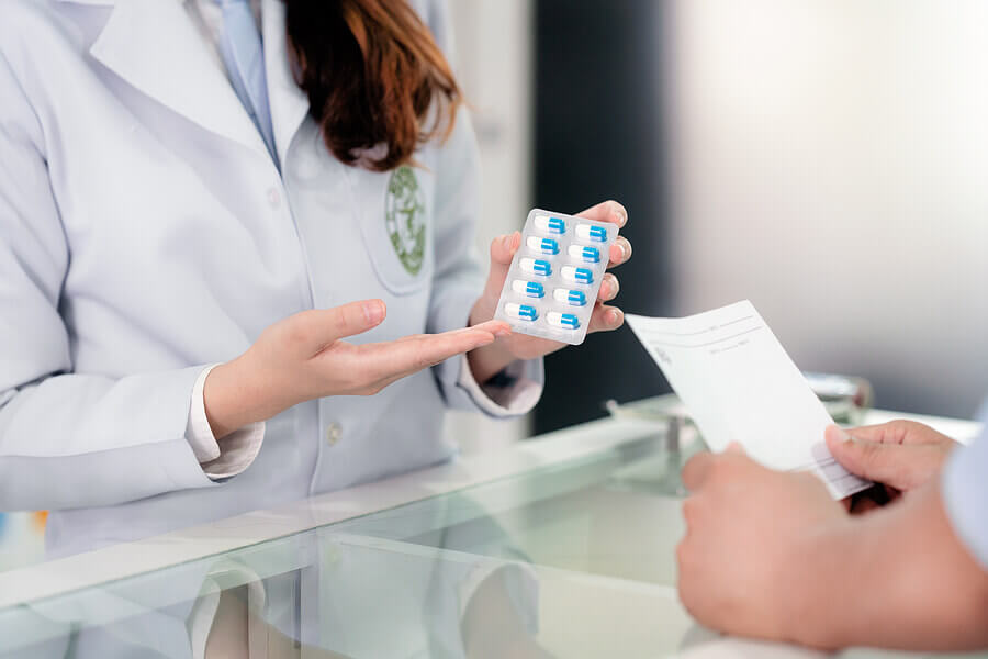 Pharmacist showing a pill pack to a customer.