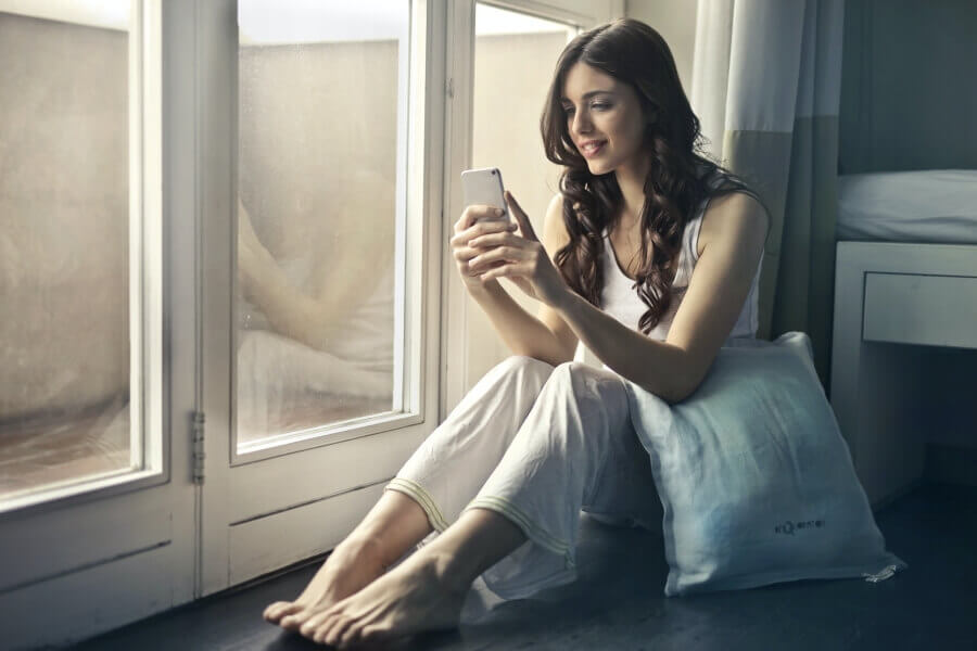 Woman sitting in a window seat looking at her phone.