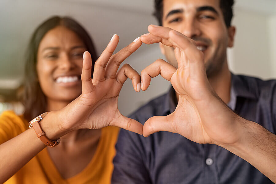 Couple creating a heart shape with their hands.