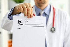 medical doctor holding a document with an Rx on it.