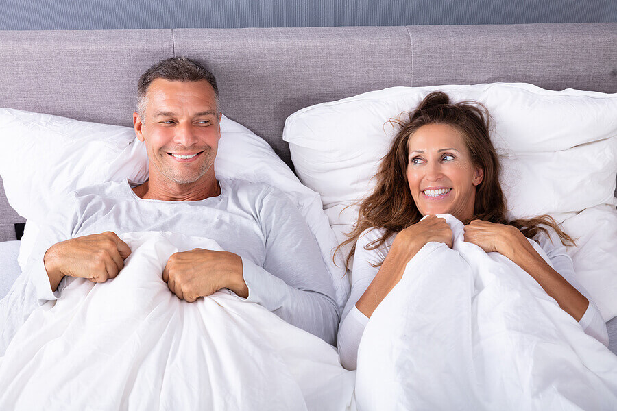Couple smiling while lying in bed.