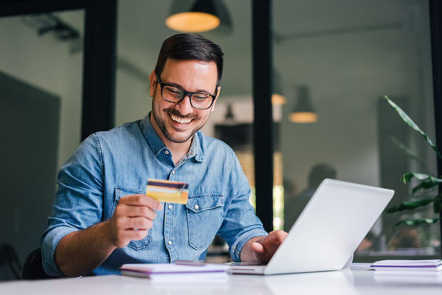 Smiling man making an online purchase with a credit card.