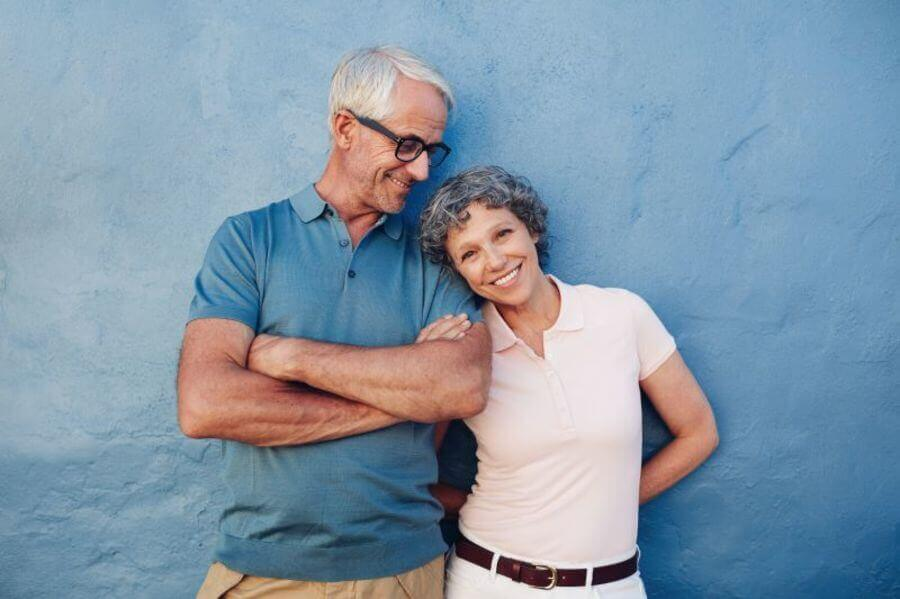Happy couple leaning against a wall