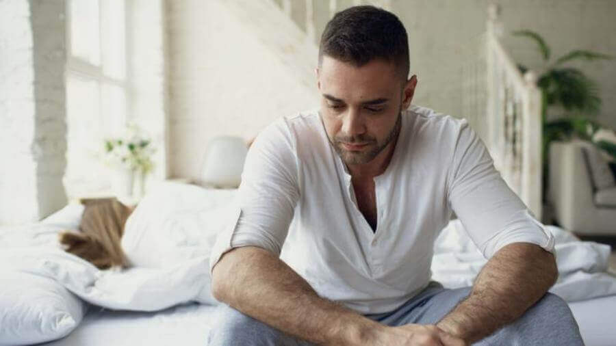 Man sitting at the edge of his bed looking down