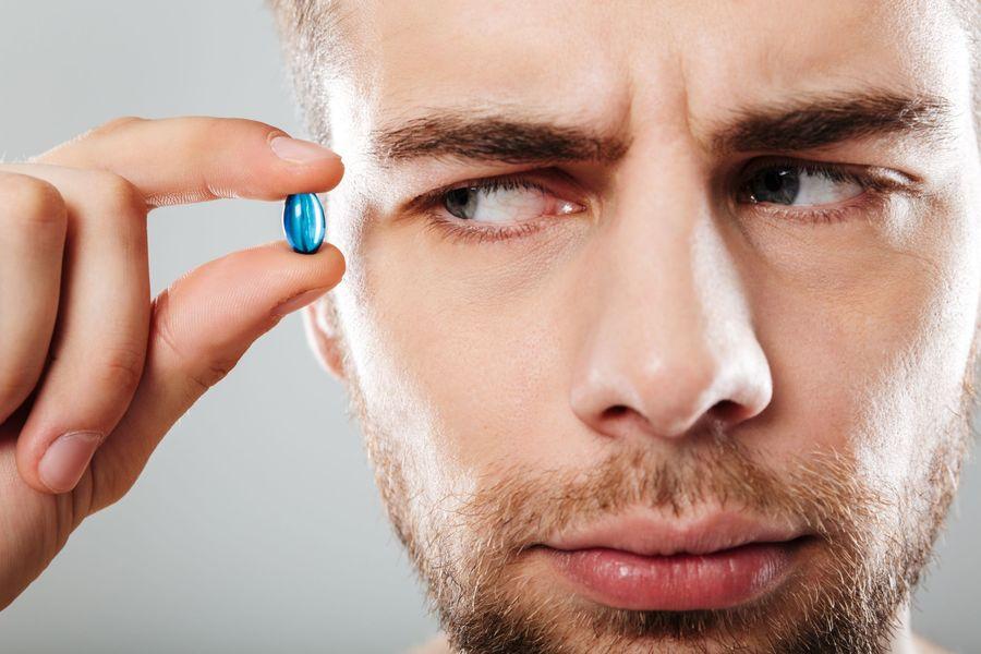 Man Eyeing Pill Suspiciously