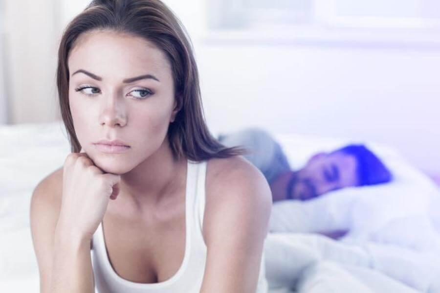 Woman sitting at the edge of her bed