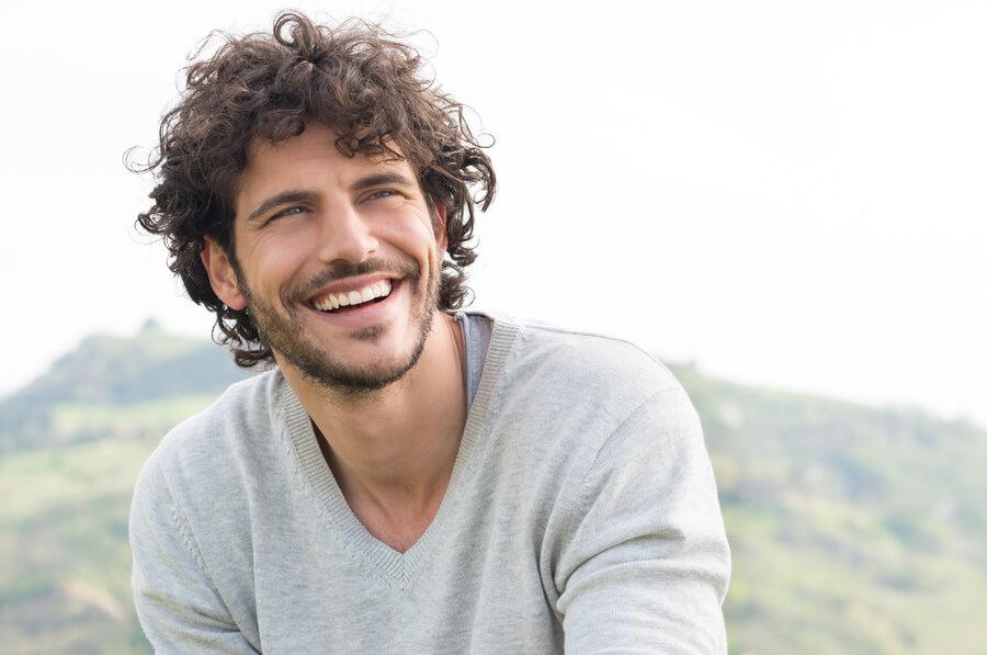 Smiling man sitting outside